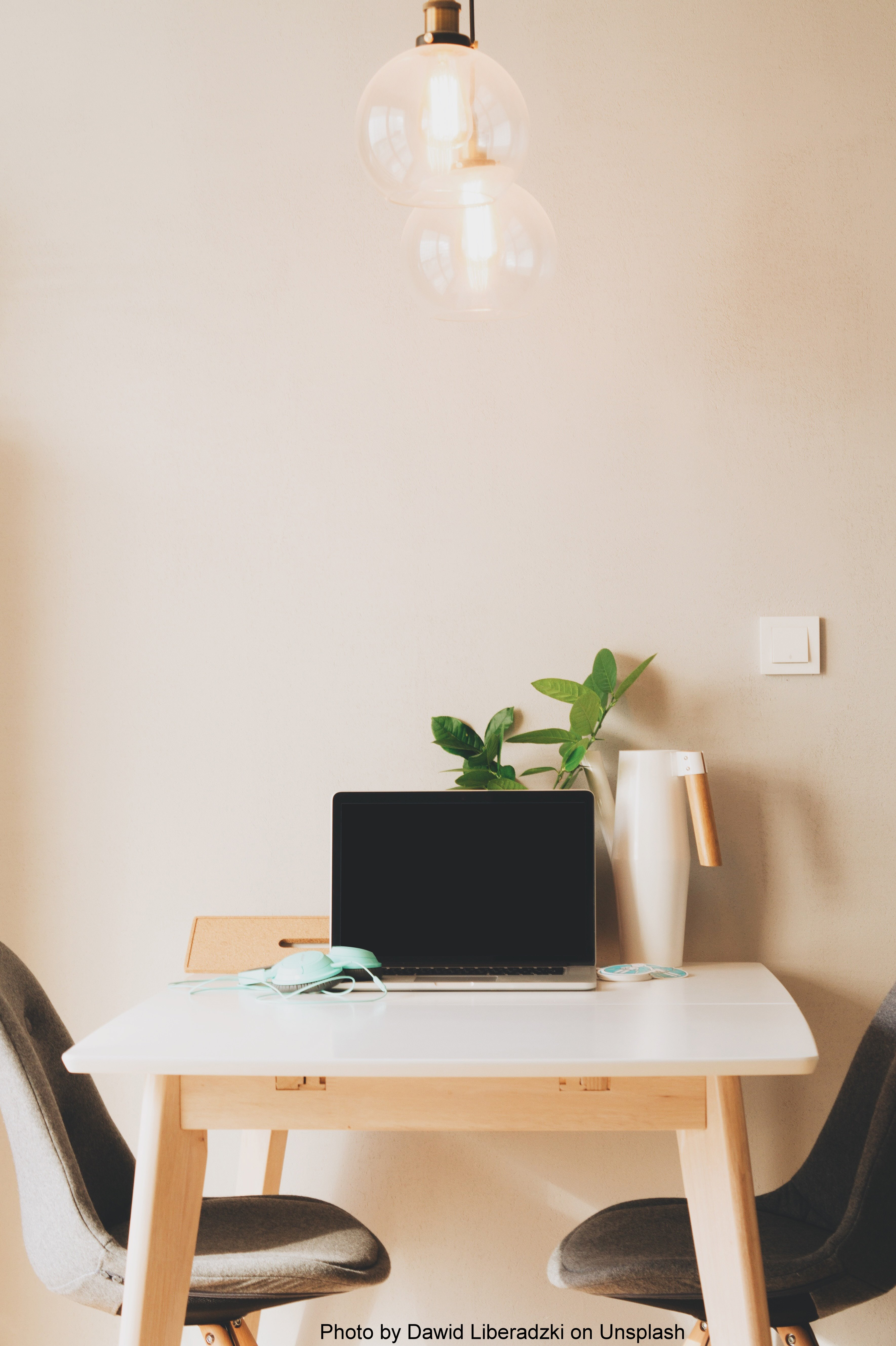 A desk and two chairs, pushed against a baren, white wall. On the table is an opened laptop, a pair of seafoam colored headphones, a white canister, and a plant. Above the desk are two, lit lightbulbs, powered by a motion sensor switch, above and to the right of the table