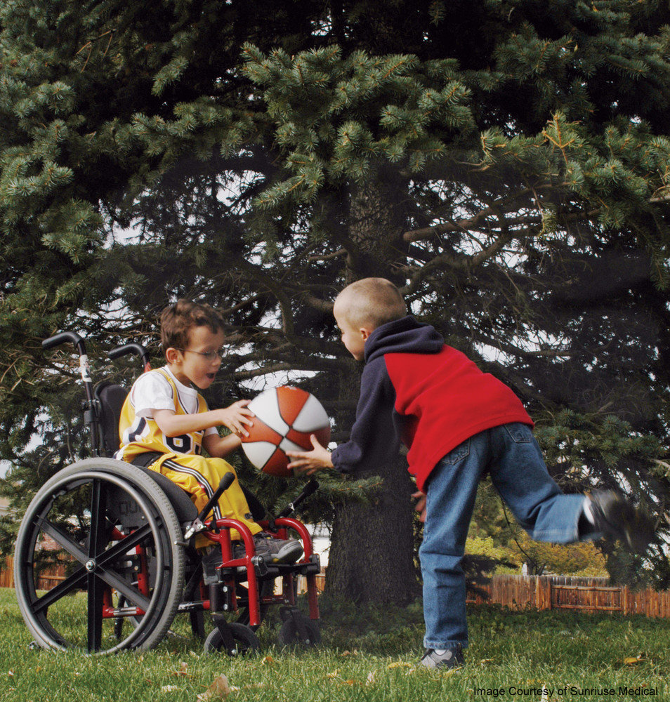 Two boys playing in a yard, with a basket ball. One is in a wheelchair, handing the ball to the other, who running to grab it
